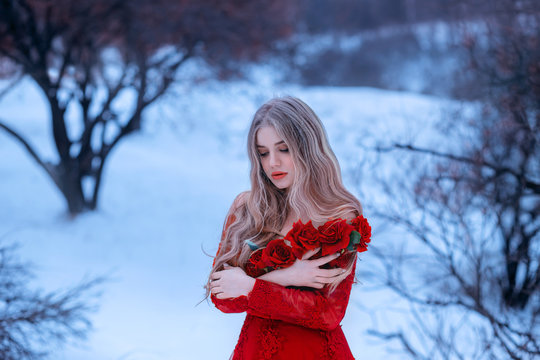 magical image of attractive blonde girl in gorgeous red dress decorated with flowers, Rose princess trying to keep warm in snowy forest, wonderful work of make-up by visagiste and photographer
