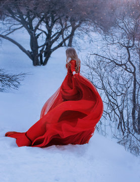 fair-haired lady does not show her face in the photo, dressed in gorgeous amazing red wonderful dress with long train and bare shoulders, flaps her hem f her gown, creates magical wave of fabric