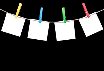Blank white paper lists pinned with clothespins on rope isolated on black background. Blank white paper cards hanging with clothes pins with rope on black background. Empty space. Copy space