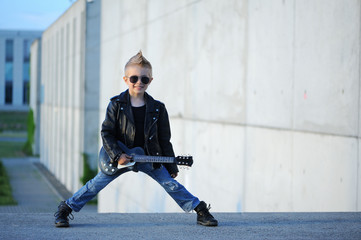 A  little, cute boy guitarist in leather jacket and sunglasses  playing guitar.  Young idol. Children's interests and hobbies. Be like a rock star.