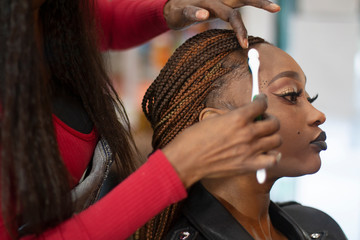 A black hairstylist combing with a toothbrush a beautiful black model.