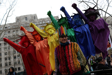 Pat Oleszko wears her costume representing women of all colors with the Statues of Libery behind her, at the Women's Unity Rally in Foley Square in New York City