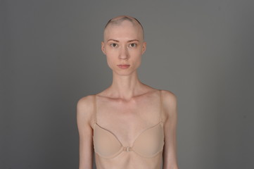 bald girl in beige lingerie posing on grey background