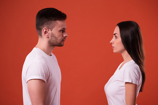 Side view photo of young serious couple standing face to face in studio