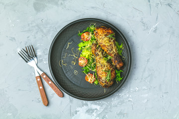 Chicken drumstick in a black ceramic plate with orange and rosemary