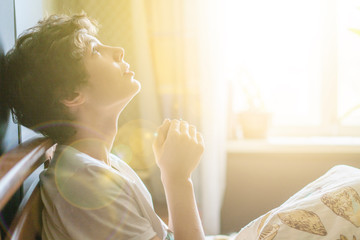 young man is praying in bed at home against the window b