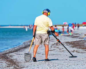 Person working metal detector on the beach