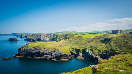 Acrylic Prints Island Merlin's Cave, green rocky cliffs, dramatic landscape with Atlantic Ocean / Celtic Sea view from Tintagel castle island in Cornwall, United Kingdom, UK. Western England coastline summer holidays.