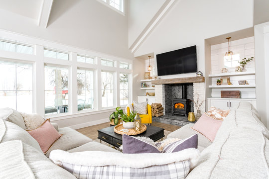 A modern farmhouse family room with transom windows and a wood burning stove.