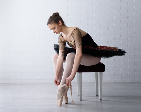 Portrait of young beautiful ballerina tying her shoes