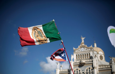 A Mexican flag with the image of the Virgin of Guadalupe is displayed as Catholic pilgrims take part in a religious ceremony before leaving for Panama to participate in the third World Youth Day with Pope Francis, in Cartago