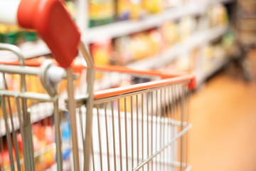 Shopping trolley cart with shallow DOF against supermarket aisle background