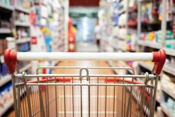 Perspective view shopping trolley cart with supermarket aisle blurred background