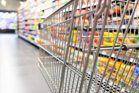 Shopping trolley cart against supermarket aisle blurred background