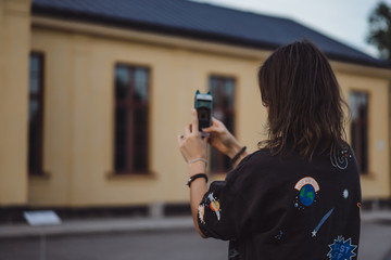beautiful young woman taking pictures on a smartphone