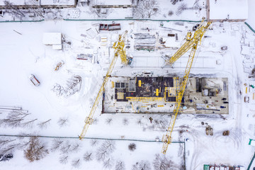 yellow tower cranes working at city construction site in winter under snow. aerial top view