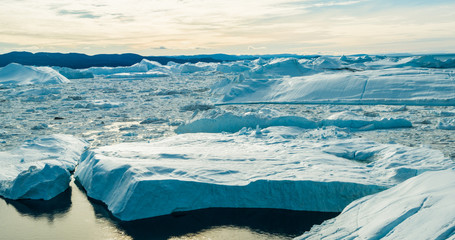 Climate Change and Global Warming - Icebergs from melting glacier in icefjord in Ilulissat, Greenland. Aerial image of arctic nature ice landscape. Unesco World Heritage Site.