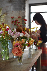 Flowers on Table in Floral studio with woman in background