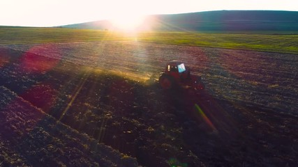 Wall Mural - Sunset over harvest fields with cultivating tractor. Farmer plowing stubble field.