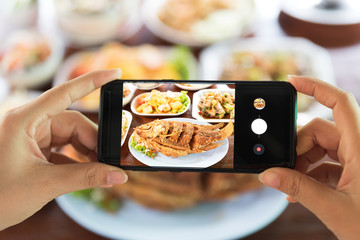 Woman taking a photo of food with smartphone in restaurant.