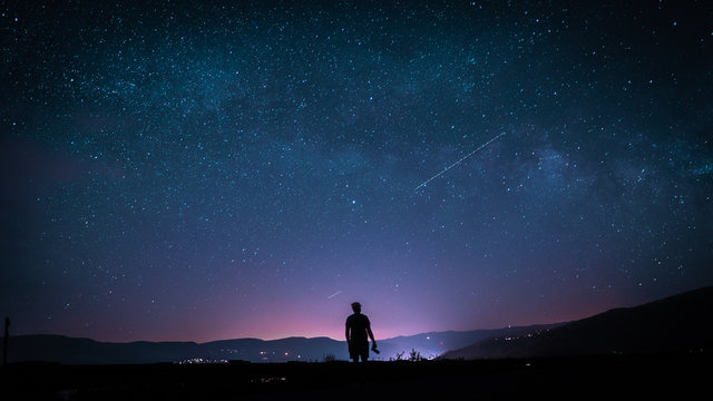 silhouette of man on top of mountain with stars