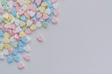 Valentine pastel colourful heart candies in a left corner pile