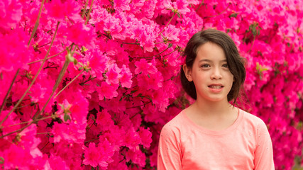 Young Asian teen standing in front of pink azalea flowers in tshirt on hot spring day