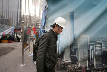 A worker walks outside the construction sites in Beijing's central business area