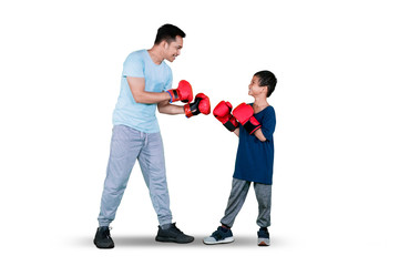 Boy doing boxing exercise with his father