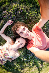 A man and a woman are lying on the grass.