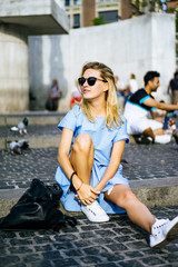 A girl is sitting on Dam Square. Amsterdam.