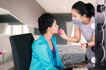 Young woman doing visage makeup to her client