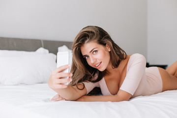 Portrait attractive young girl laying on bed in apartment. She takes a selfie portrait and smiling to camera