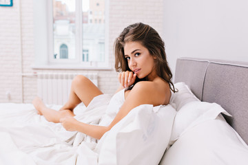 Amazing charming girl with long brunette hair chilling in white bed in modern apartment. Sexy look, positive emotions, waking up in the morning, good mood, beautiful model