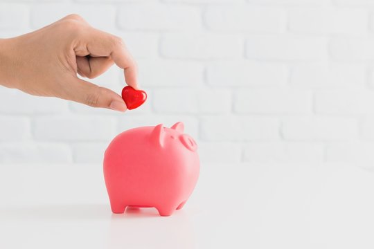 Man's hand putting red heart in to piggy bank metaphor saving love for lover or family in every day.Concept of happy relationship.