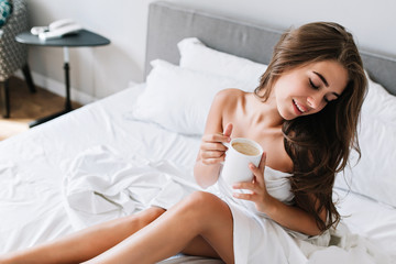 Portrait young brunette girl with naughty legs and shoulders on white bed. She holds cup, keeps eyes closed, looks satisfied