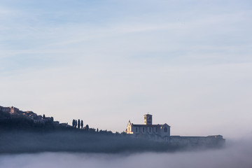 A view of St.Francis church in Assisi in the middle of mist beneath a blue sky with clouds