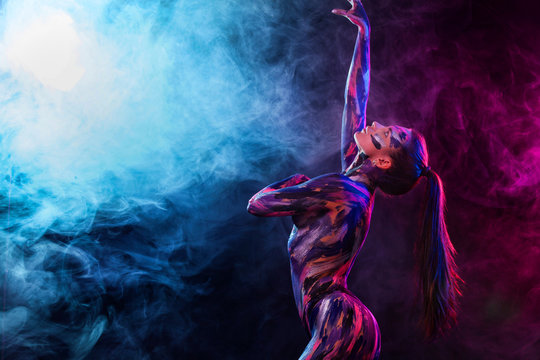 Young woman painted different colors. Inspired dance to music. Body art colorful. An amazing woman with art fashion makeup.