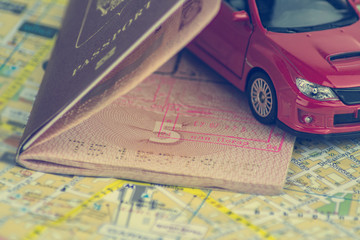The concept of auto travel, passport, model of a red car on a background map