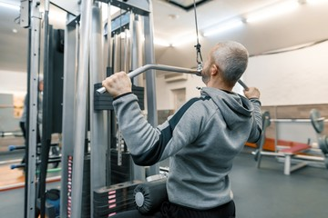 Adult age man working in training gym. Sport rehabilitation, age, healthy lifestyle concept.
