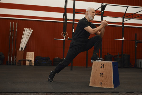 Side view of handsome energetic senior retired male with gray beard doing crossfit workout in gym, working on legs muscles, stepping up on wooden platform, having concentrated focused look