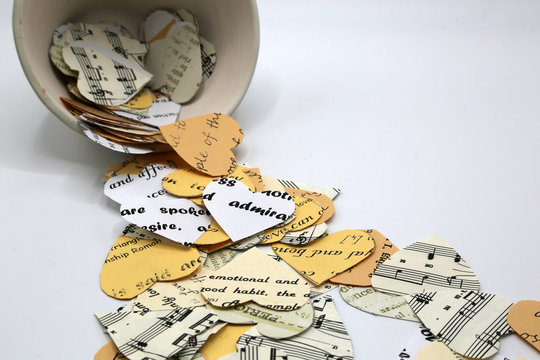 Hearts of paper different colors and textures. Musical notes, words on white, creamy beige paper hearts.One red heart.