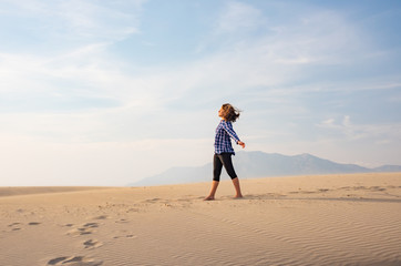 Girl walks on windy sand desert. Fridom and relax concept