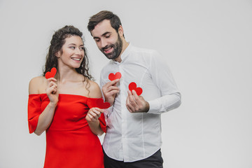 Beautiful attractive, cheerful, positive pair. Married. Spouse. Hold hands, hiding the closing eyes of the little small cards.