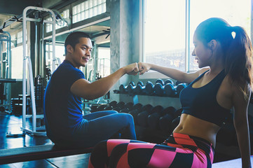 Fitness man and woman giving each other a high five after the training session in gym. Fit couple high five after workout .
