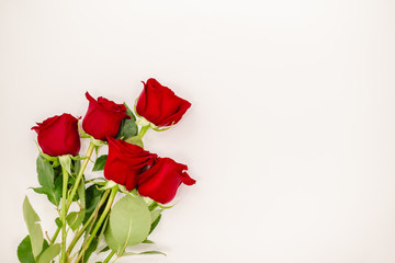 Bouquet of red  roses with a red ribbon. Eights march woman's day, holiday. Flowers on a white background copespace. Horizontal top view