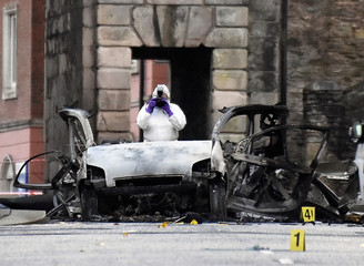 Forensic officer takes a photograph of the scene of a suspected car bomb in Londonderry