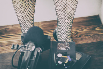 video camera cassette, flash drive lying on the table. girl in tights in a large cage. pornography photography concepts