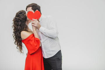 Young tender and in love couple. Hold a paper red heart in your hands. During this they kiss and hide behind the heart. Dressed in red dress and white shirt.