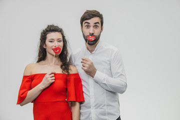 Sweet woman and man hold red fake lips on a stick. Have fun The wife is dressed in a red dress, a man in a white shirt.